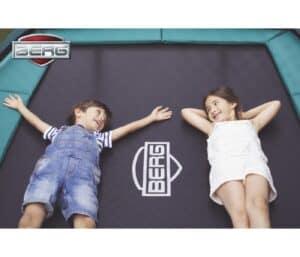 børn ligger på aflang trampolin