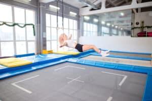 pige der kommer på en stor indendørs firkantet trampolin